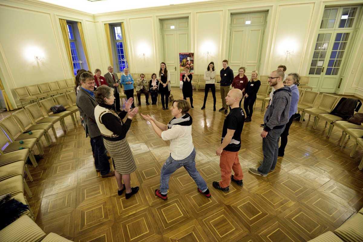 Leute stehen im Kreis und spielen ein Klatschspiel.