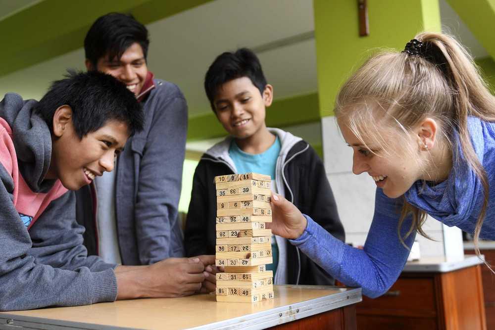 Volontärin spielt mit Jugendlichen Jenga