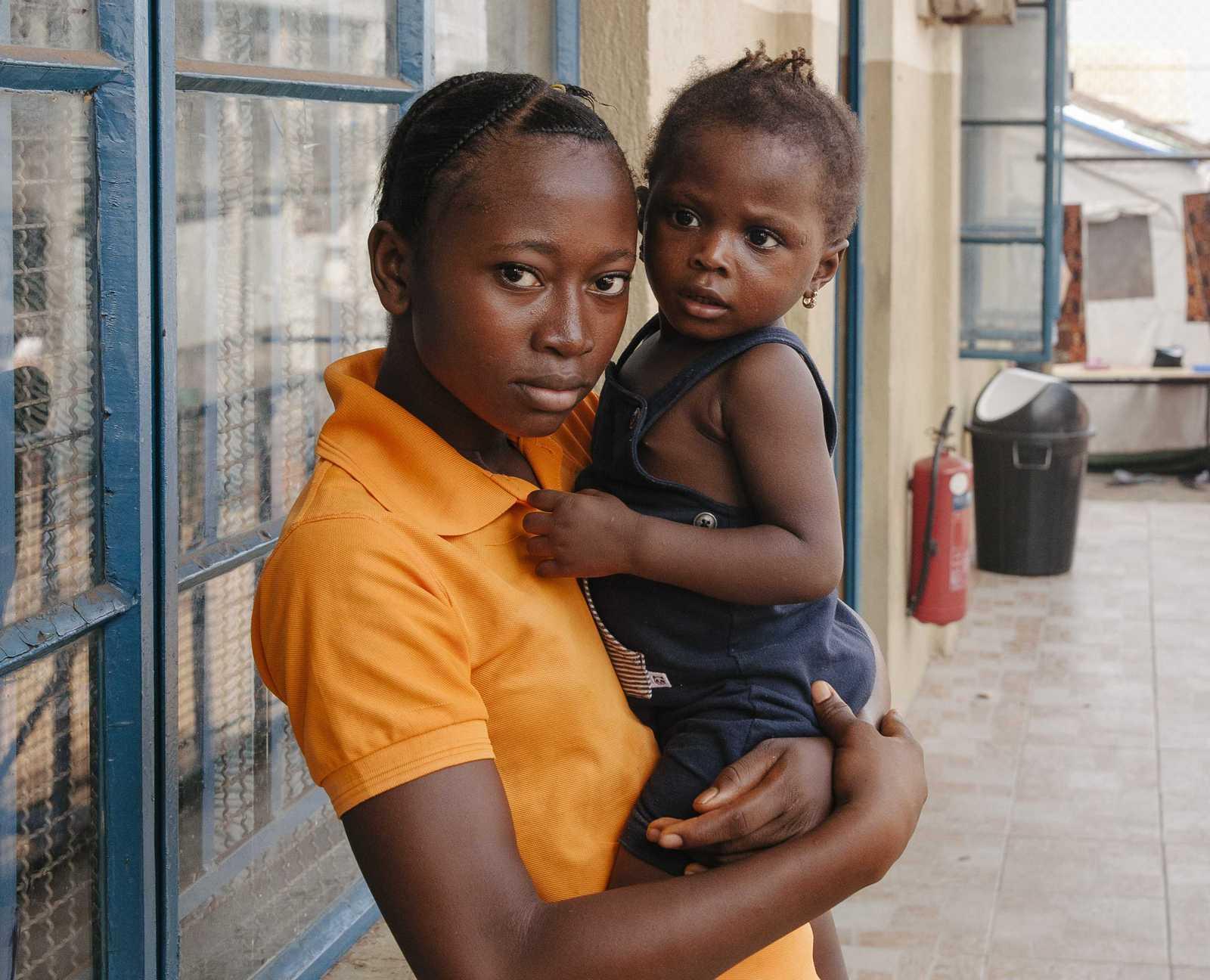 Yaema trägt ihre kleine Schwester Fatu auf dem Arm