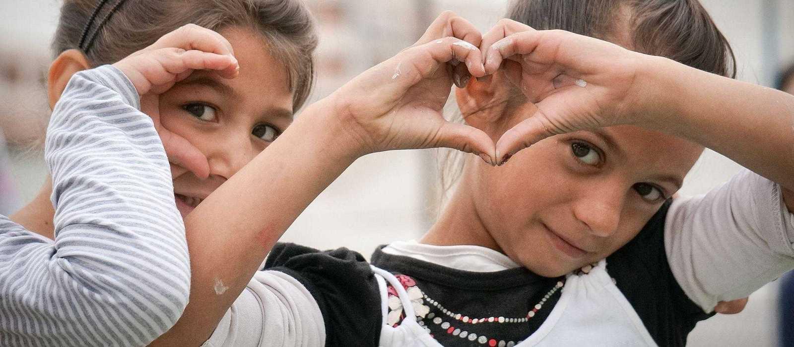 Zwei Mädchen. Eine zeigt ein Herz mit Händen.