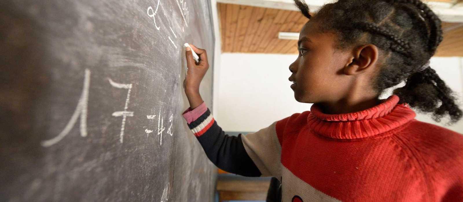 ein Mädchen rechnet eine Aufgabe an der Tafel