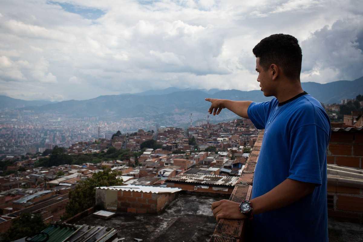 Jugendlicher zeigt auf die Stadt Medellín