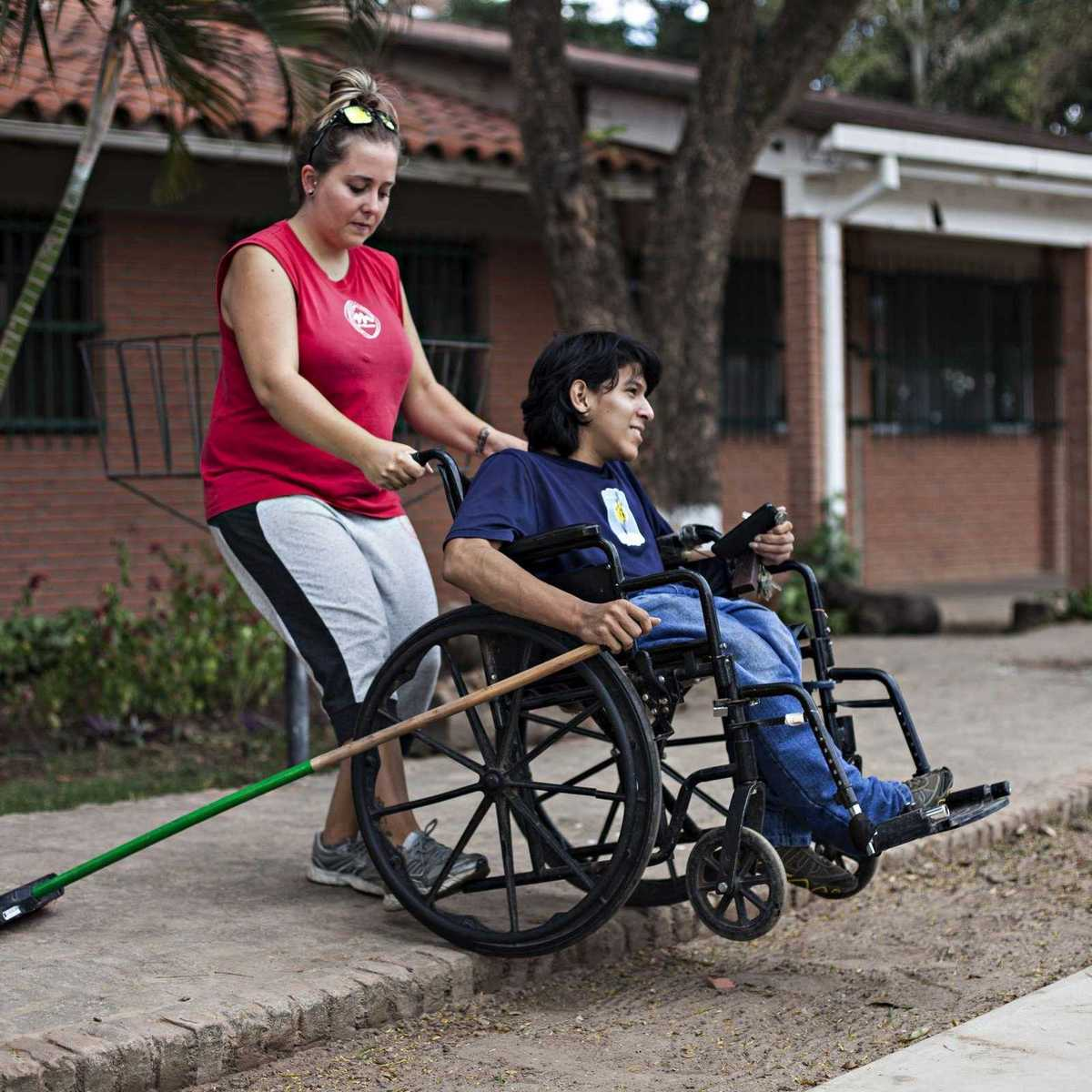 Erziehrin kümmert sich um einen Jungen im Rollstuhl