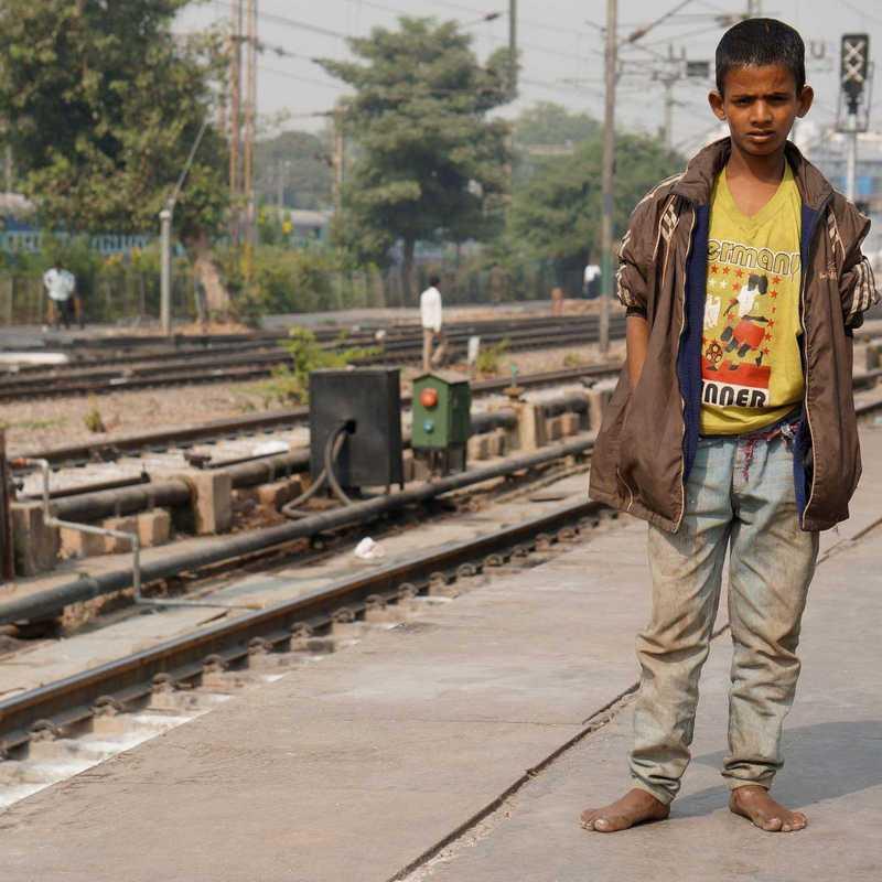 Straßenjunge in Indien an den Bahngleisen