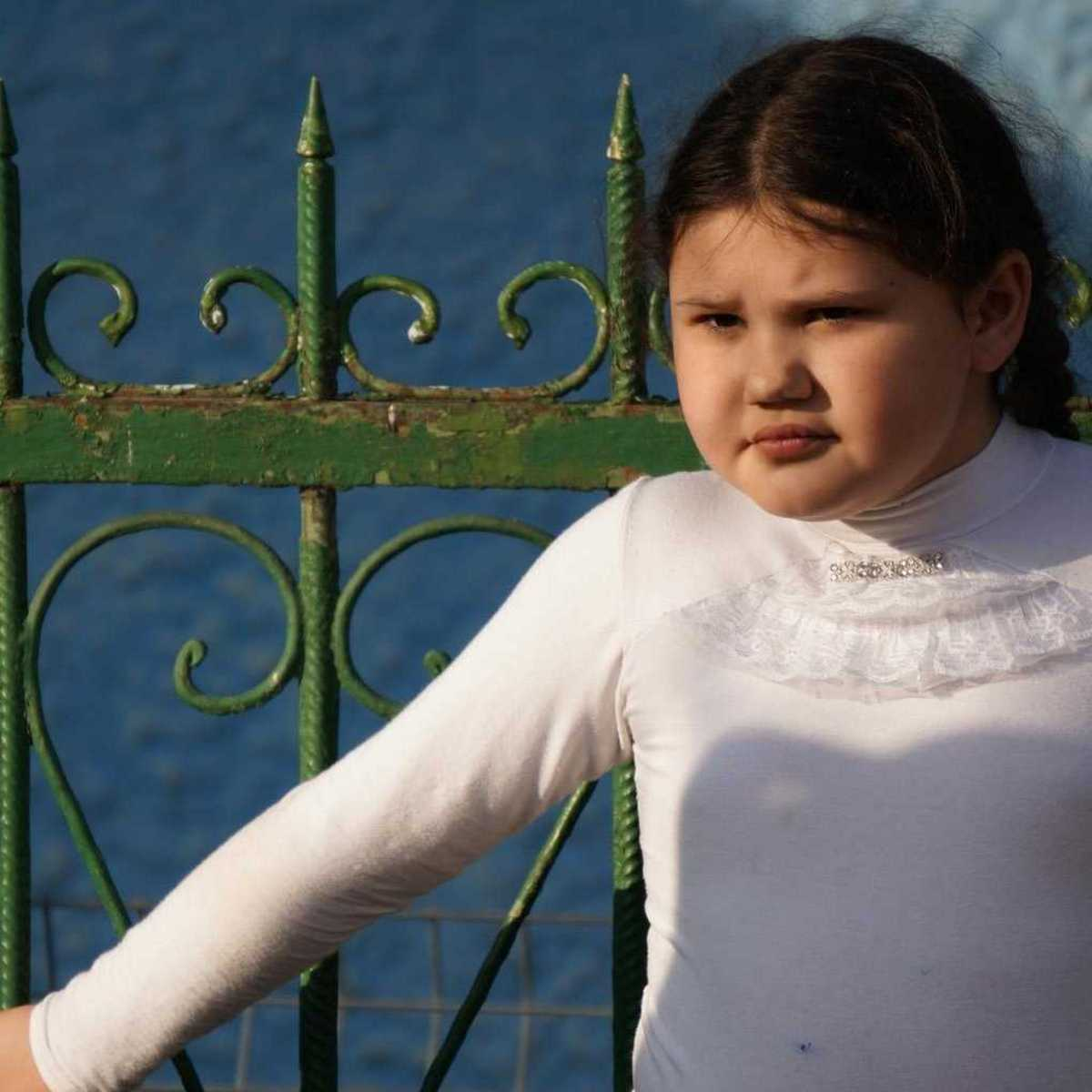 Anna steht vor einem grünen Zaun