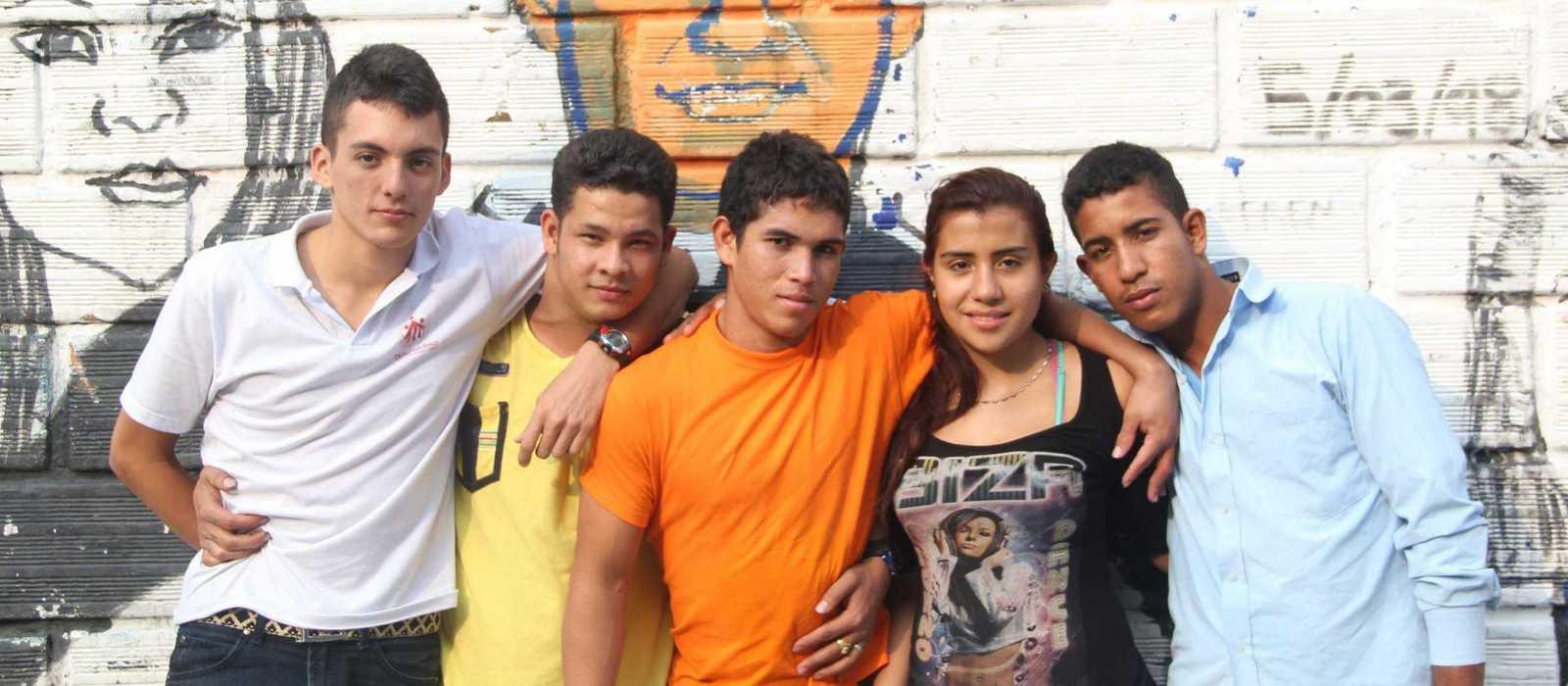 Jugendliche in der Ciudad Don Bosco vor einem Grafiti von Don Bosco