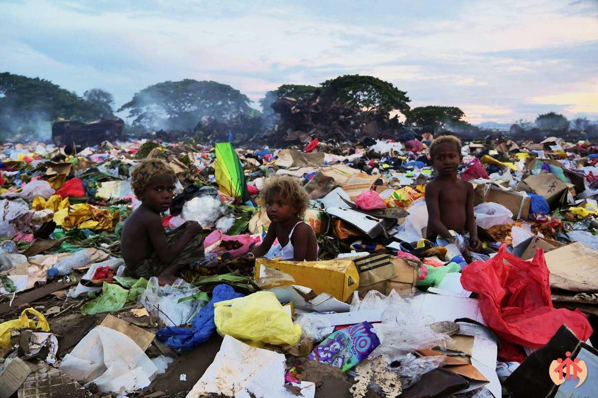 Kinder sitzen auf einem Müllhaufen