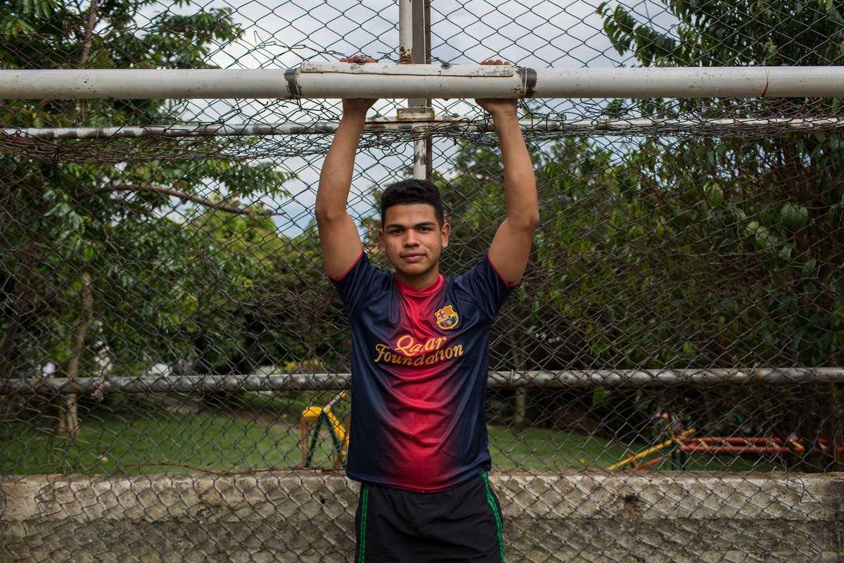 Junge hängt mit Armen an einem Fußballtor
