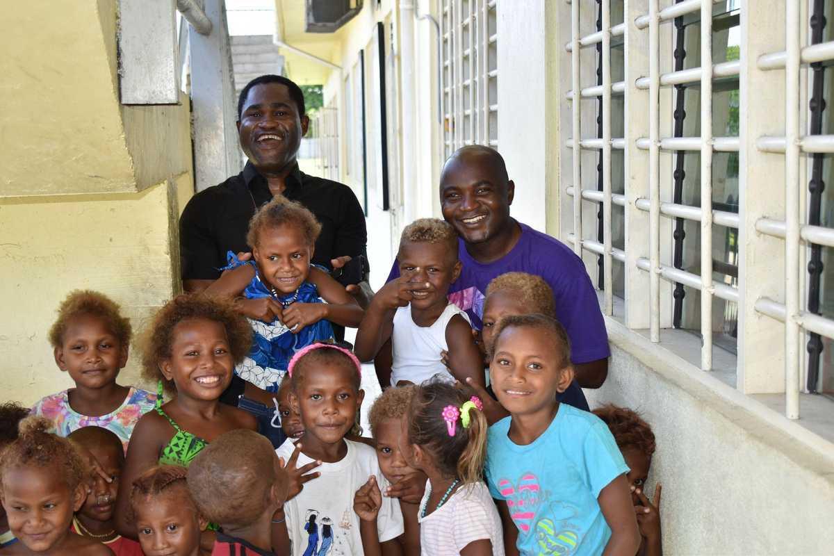 Zwei Don Bosco Padres mit Kindern in der Schule