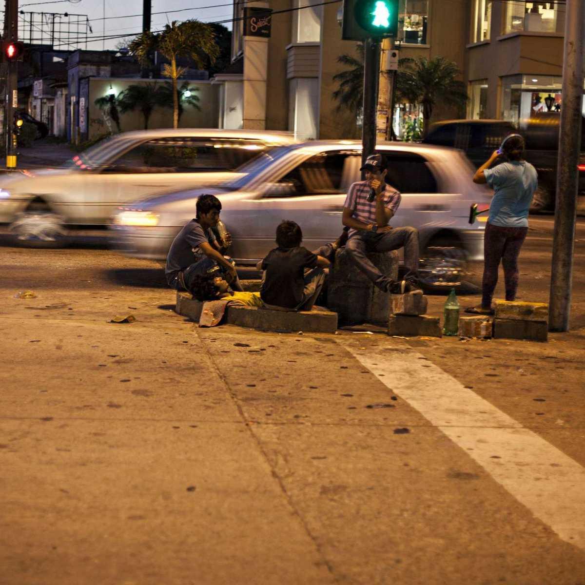 Autos fahren an vier Straßenkindern vorbei die da sitzen und Drogen nehmen