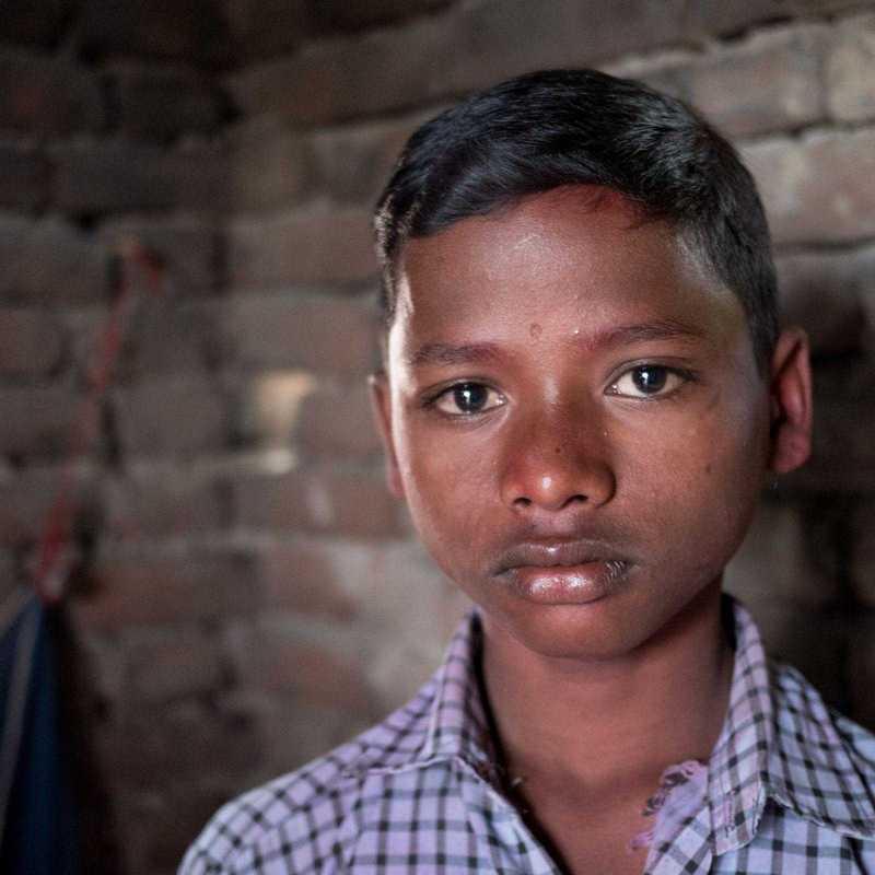 Ein Junge steht in seinem Zuhause, einer einfachen Hütte