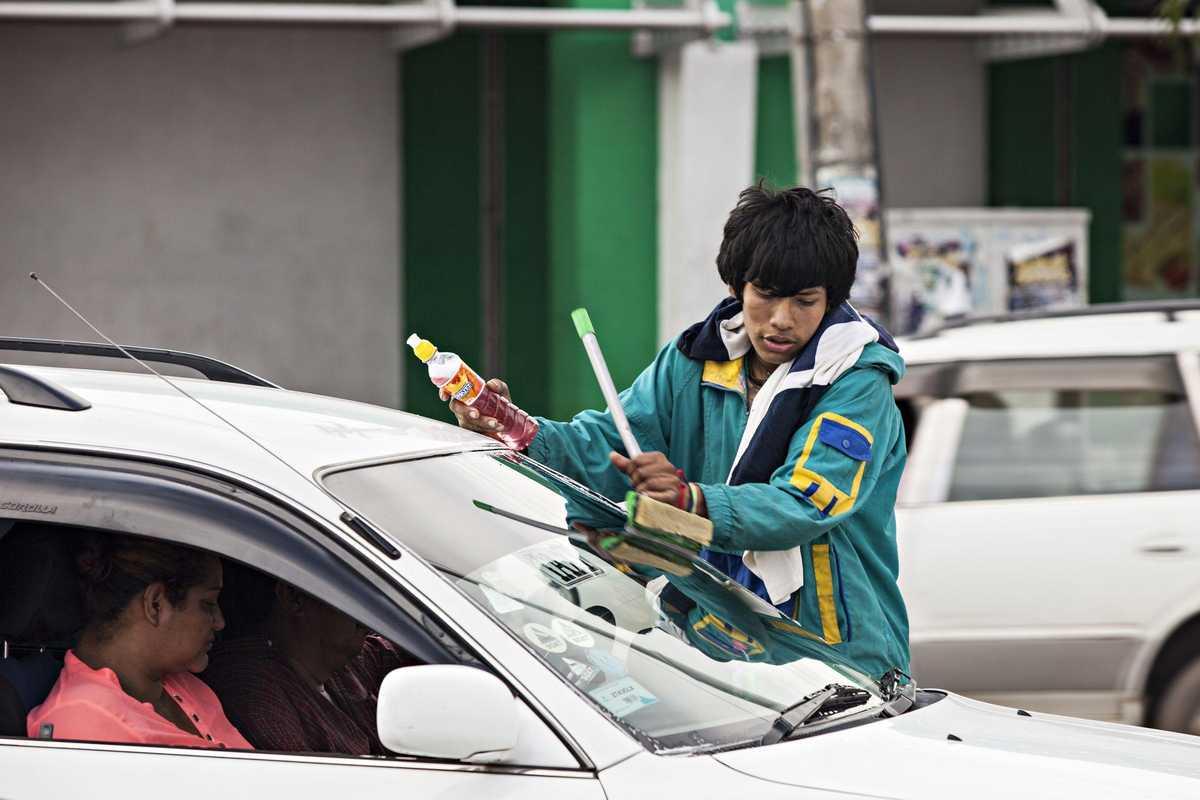Ein Junge putzt die Scheiben eines Autos