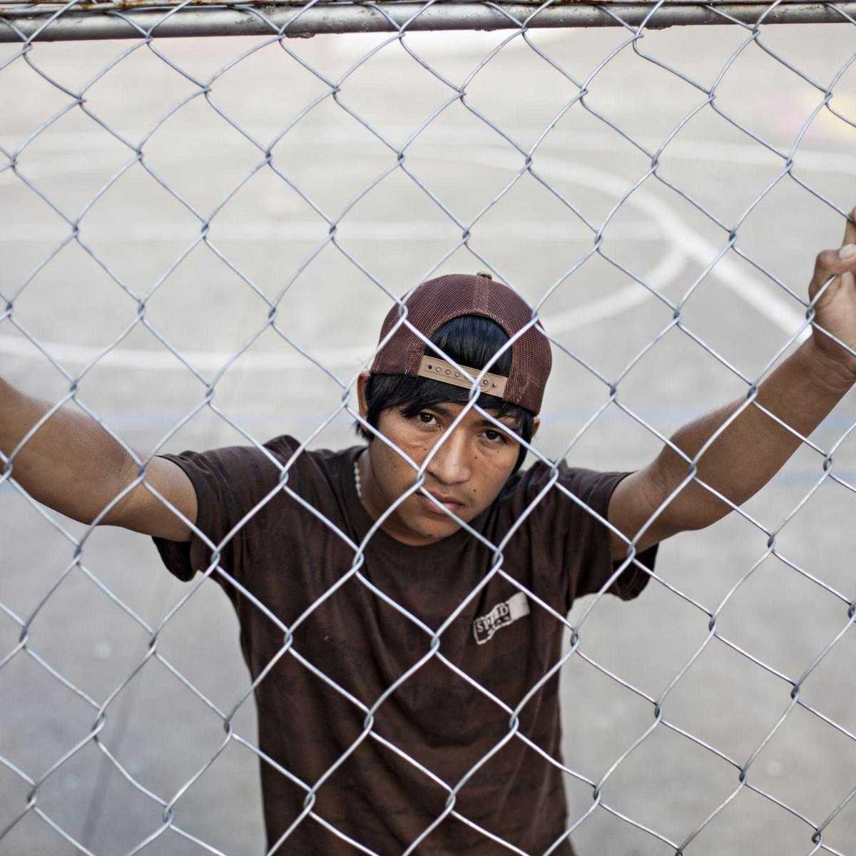 Straßenkind in Bolivien steht hinter einem Zaun