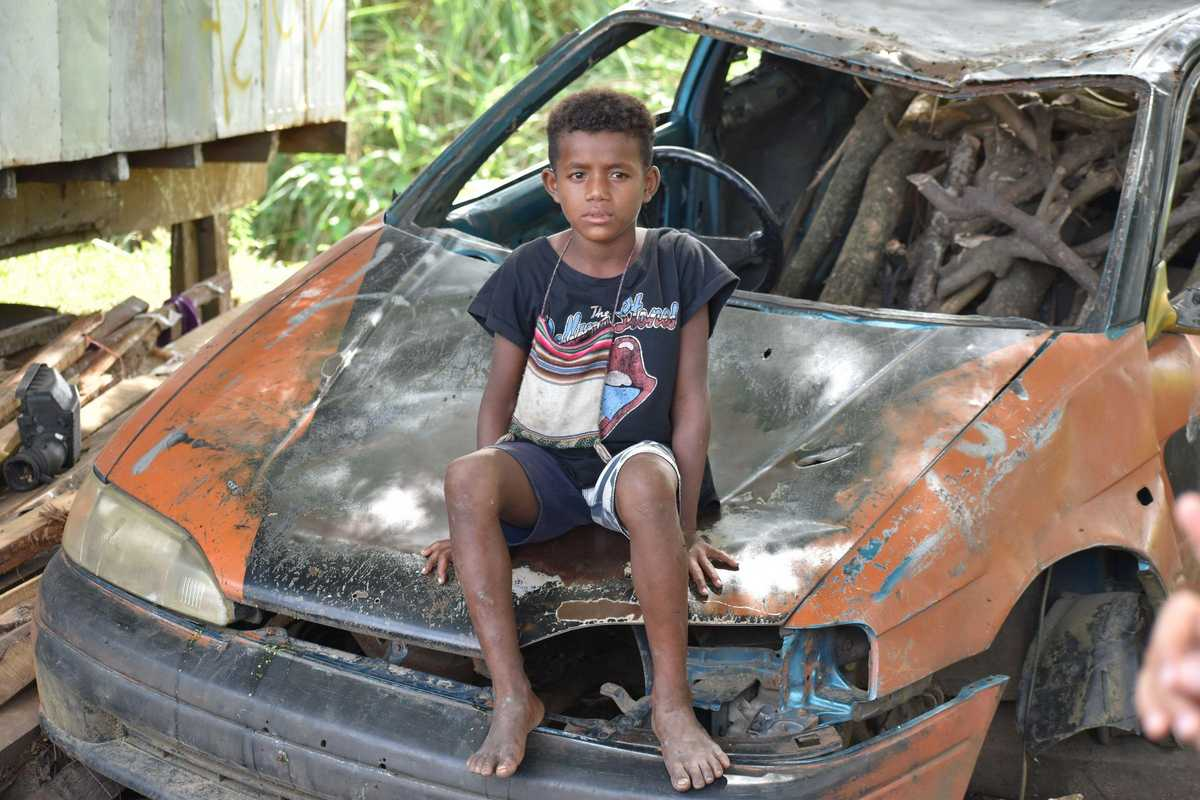 Junge sitzt auf Auto Wrack