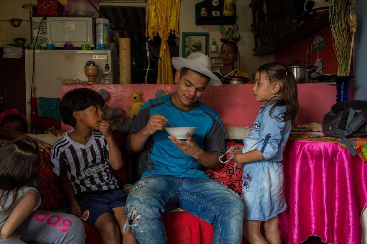 Jugendlicher und zwei Kinder sitzen auf dem Sofa und essen