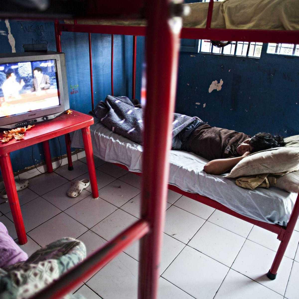 Junge in seinem Bett im Heim beim Fernseh schauen