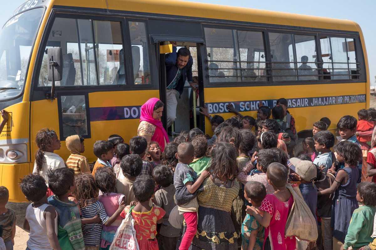 gelber Bus mit vielen wartenden Kindern davor