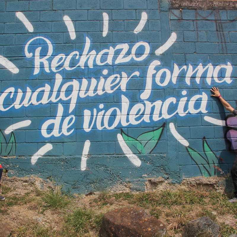zwei Jungs vor einem Grafiti das besagt: Jede Form von Gewal ablehnen