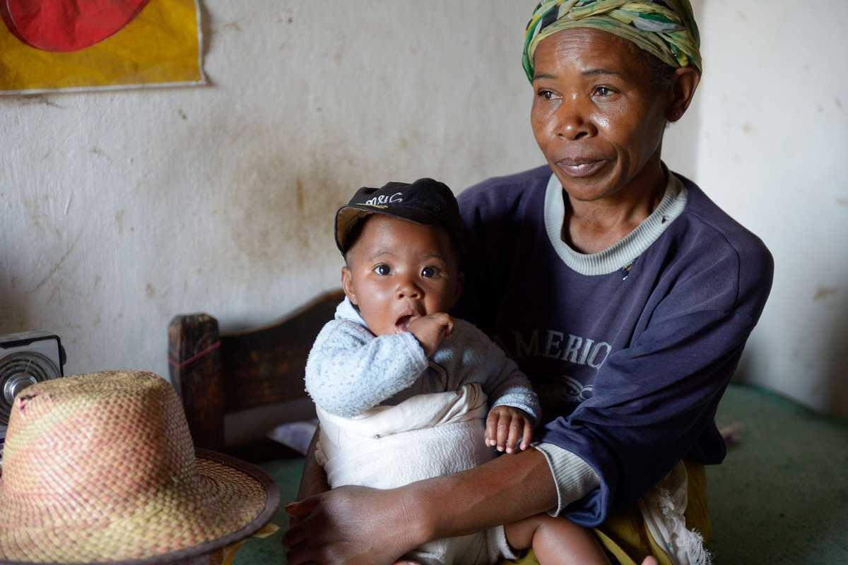 Elisas Mutter sitzt auf einem bett und hat ihren Enkel auf dem Schoss
