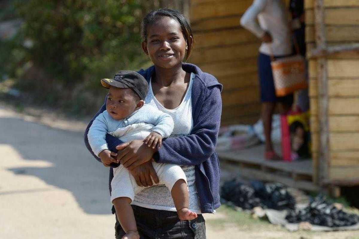 Elisa geht auf einer Straße und trägt ihren Sohn im Arm