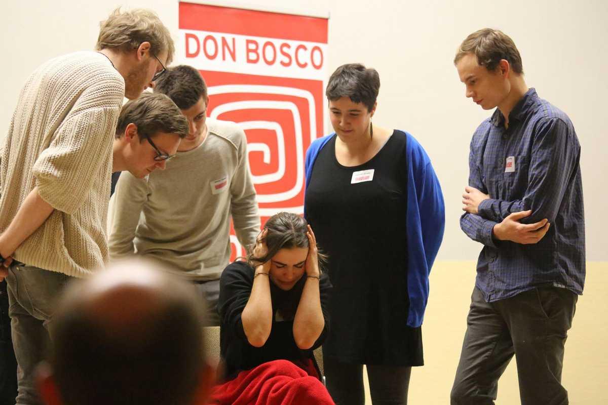 Theaterstück auf der Bühne, Fünf Menschen reden auf Protagonistin ein.