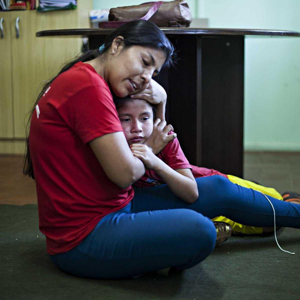 Erzieherin umarmt liebevoll ein Kind aus dem Heim