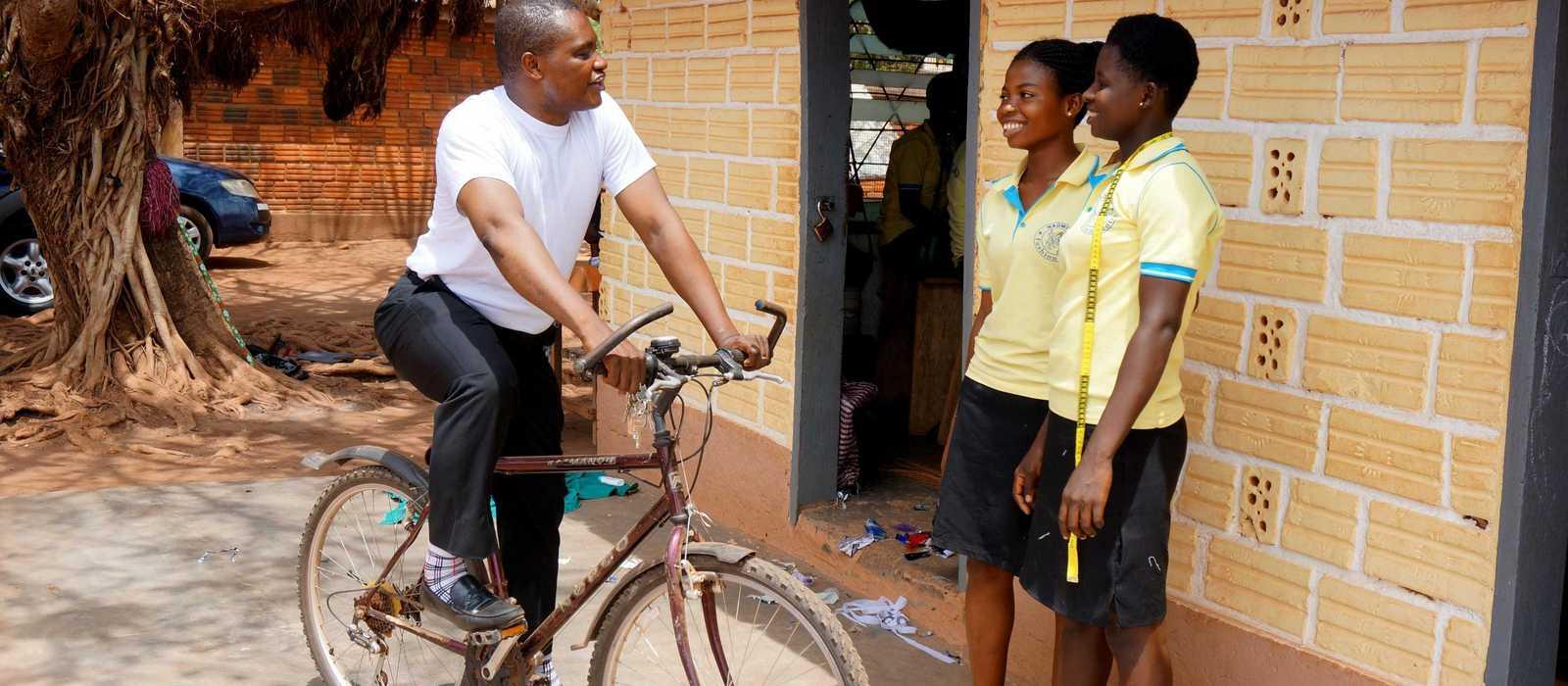 Pater Robertson Sung SDB auf seinem Fahrrad im Gespräch mit zwei Schülerinnen