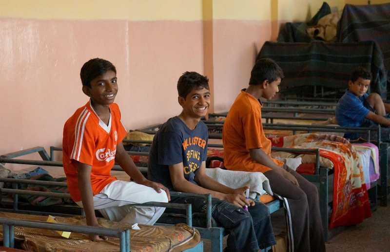 Vier Jungs sitzen auf den Betten im Straßenkinderzentrum in Delhi