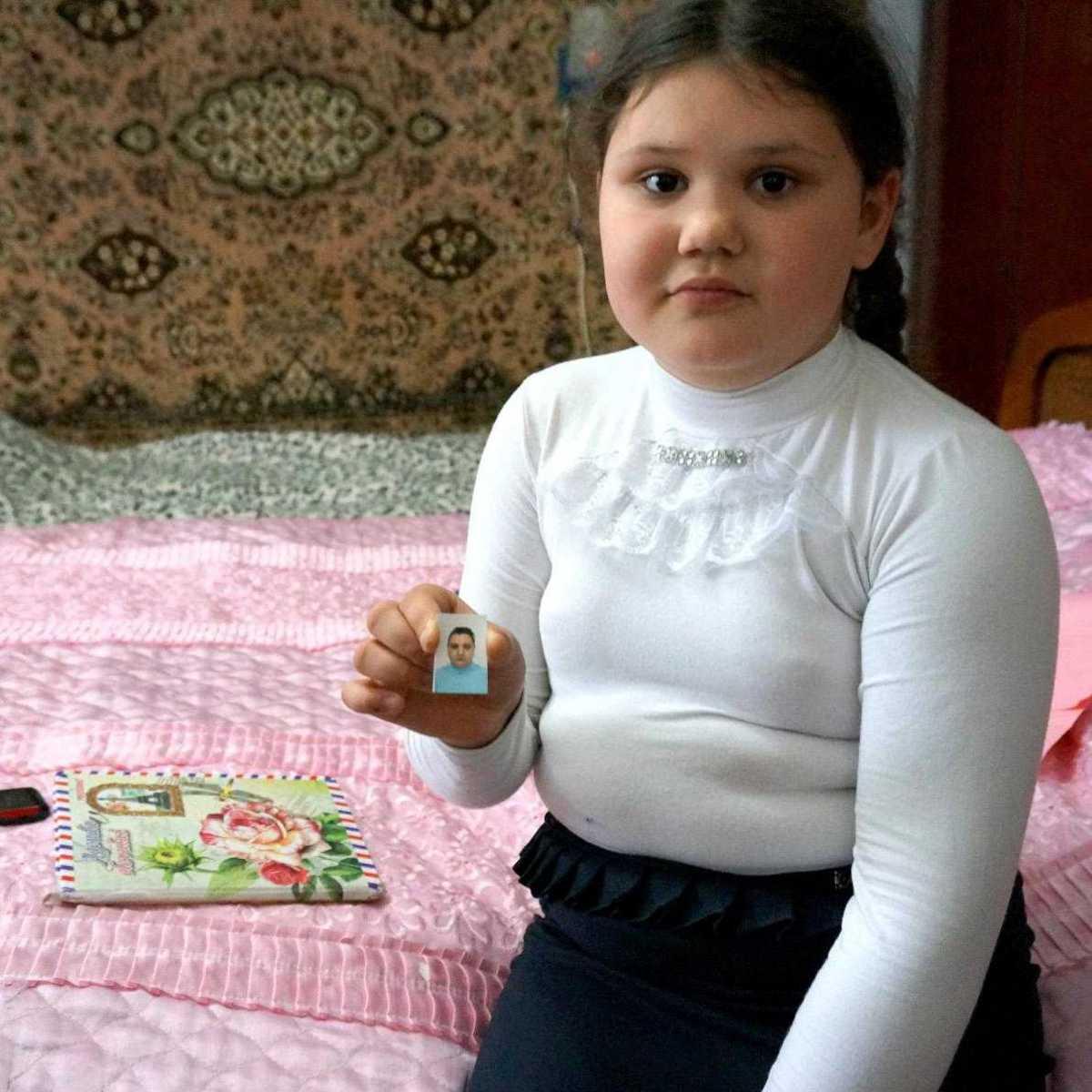 Anna hält ein Bild von ihrer Mutter in die Kamera