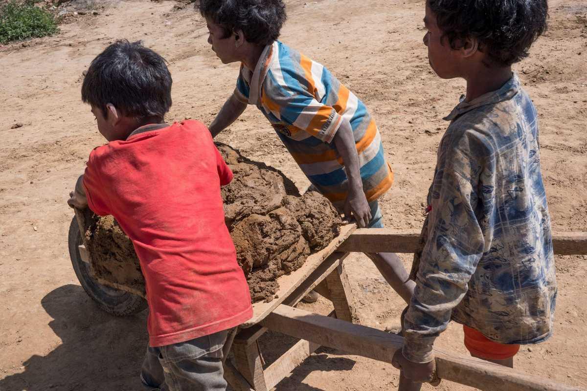 Drei Kinder schleppen Ton für die Ziegel