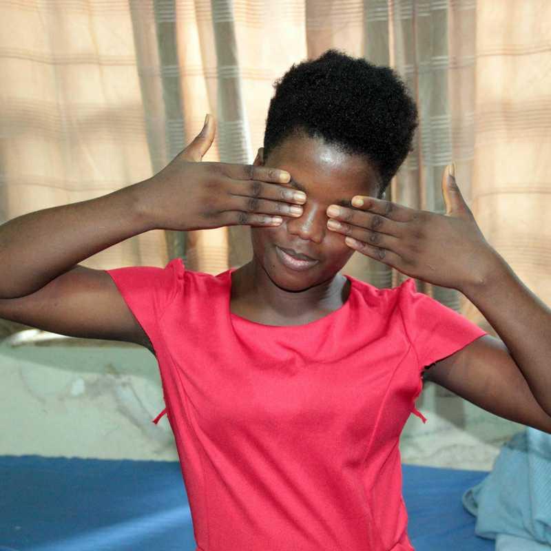 Mädchen versteckt ihr Gesicht inter ihren Händen