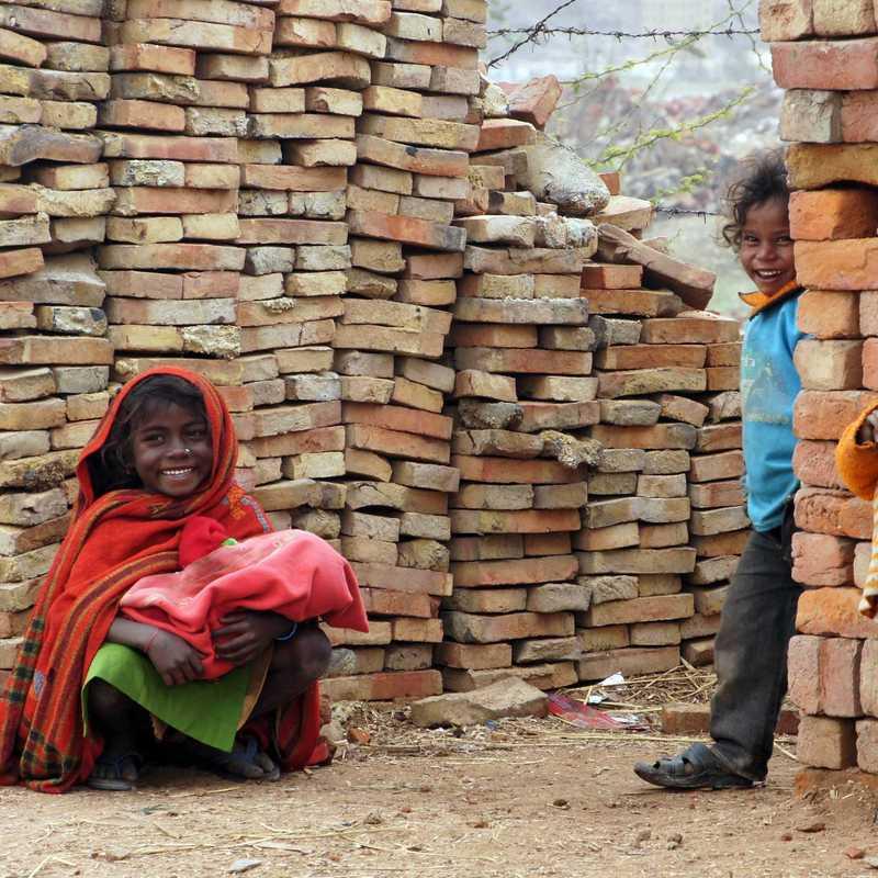 Drei Kinder stehen zwischen den Ziegelmauern in Passor