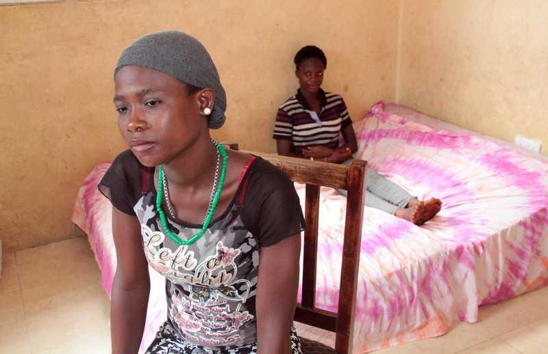 Aminata sitzt auf einem Stuhl vor einem Bett.