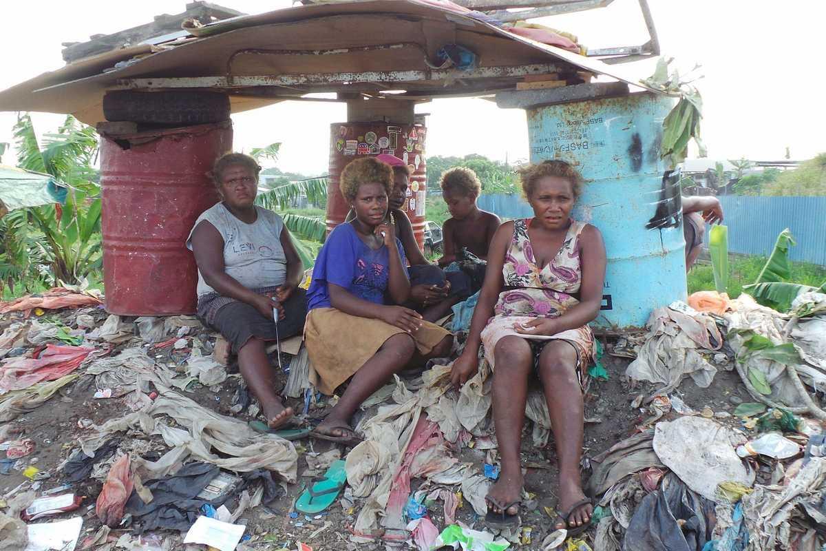 Frauen sitzen auf der Mülldeponie