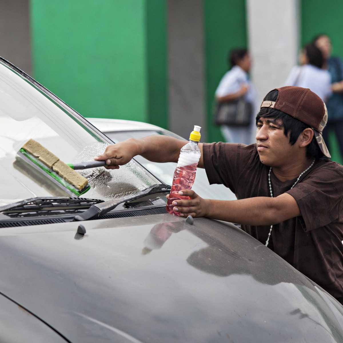 Straßenkind in Bolivien beim Putzen von Autoscheiben