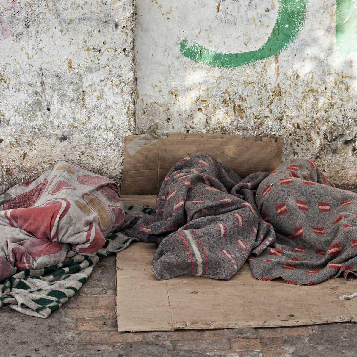 zwei Straßenkinder die auf einem Pappkarton auf der Straße schlafen