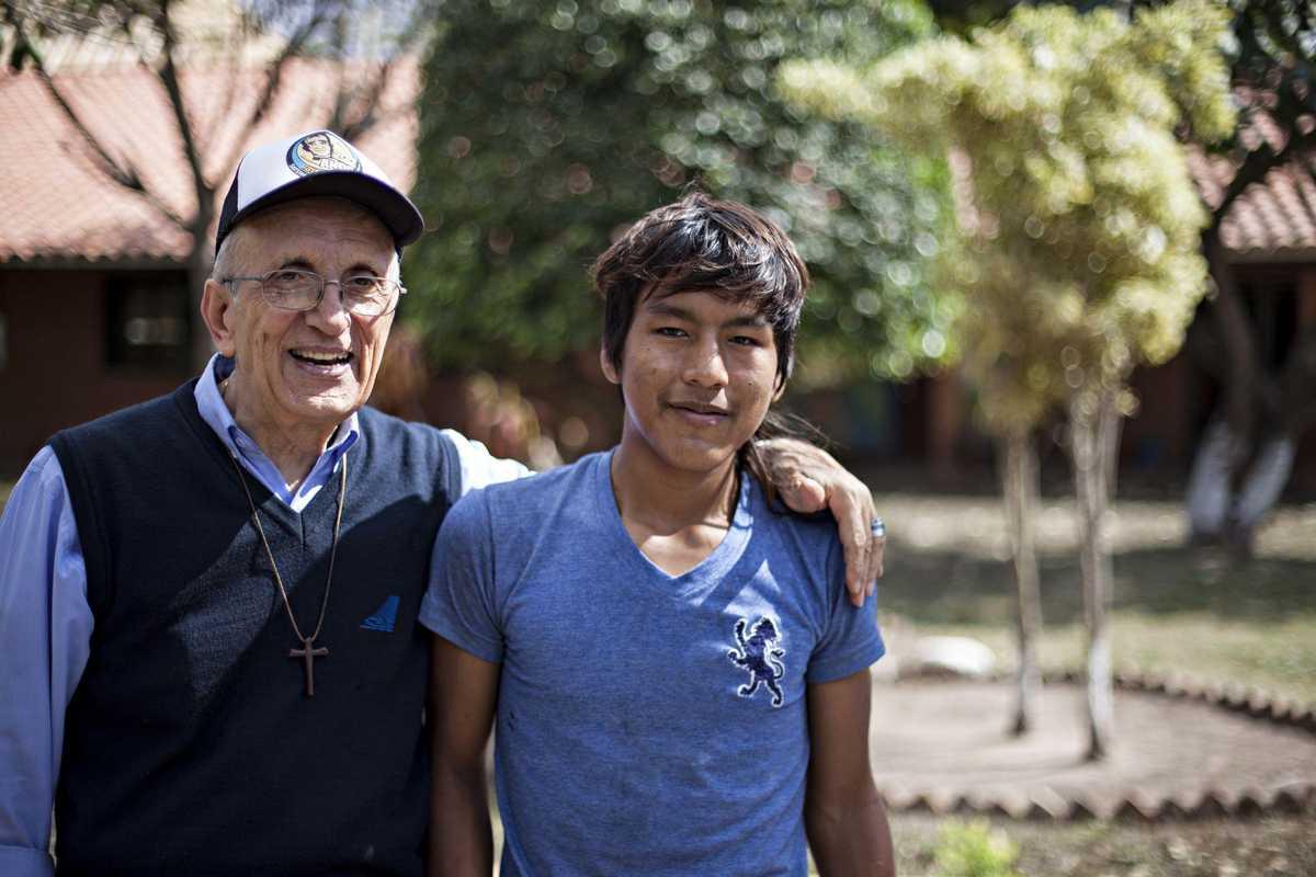 Der Pater und Leiter der Einrichtung mit einem Jungen