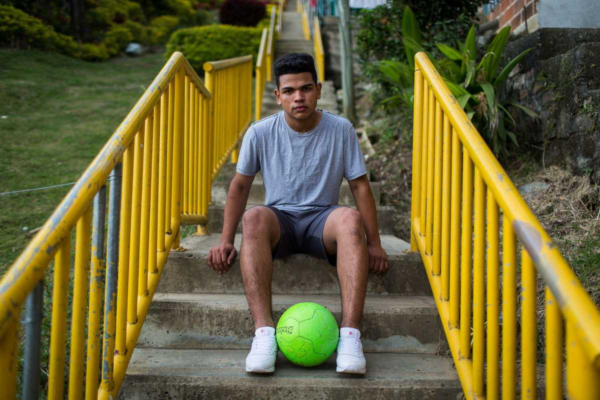 Junge sitzt mit Fußball auf einer Treppe